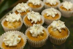 bagerit Materiel av muffin som täckas med kräm Arkivfoto