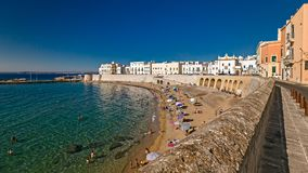 Bagers sunbathe in the beach of purity, in the historic center o. GALLIPOLI, ITALY - CIRCA JULY 2017: Bagers sunbathe in the beach of purity, in the historic Royalty Free Stock Photo