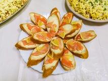 Bagett med fisken och citronen, skivor av laxen på skivor av citronen royaltyfri foto