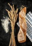 Bagett, vete och mjöl på svart bakgrund Royaltyfria Bilder