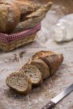 Bagettbrödsnittet i skivor med korgen av olikt bröd bildar på trätabellen royaltyfri bild