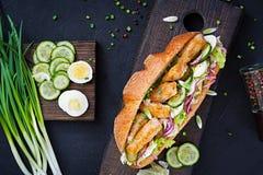 Bagettsmörgås med fisken, ägget, inlagda lökar och grönsallatsidor Arkivbilder