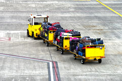Baggage cars at an airport terminal. Royalty Free Stock Photography