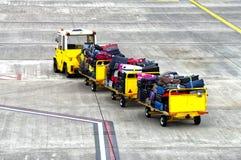 Baggage cars at an airport terminal. Royalty Free Stock Photography