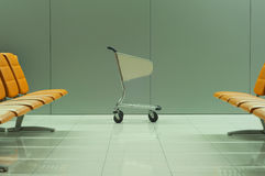 Baggage cart between the rows of empty chairs Stock Photography
