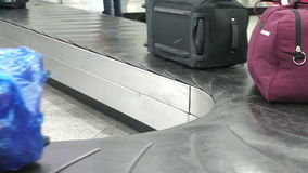 Baggage Claim in the Arrival Hall. Baggage claim area. As the conveyor belt moves suitcases and bags. The passengers take their luggage stock footage