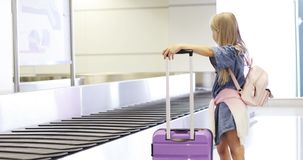 Baggage claim carousel. A little blond girl is waiting for her luggage at the airport stock footage