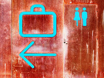 Baggage claim and rest rooms signs. Baggage claim, arrow and rest room signs at sea port on iron oxide background Stock Photo