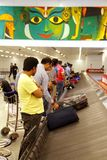 Baggage coming out on baggage carousel at Delhi Airport. DELHI AIRPORT, INDIA- AUGUST 16: Passengers identifying their baggages on carousel at Delhi Airport on Stock Images