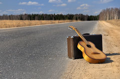 Baggage and guitar on empty road. Baggage and guitar lies on empty countryside road Royalty Free Stock Images