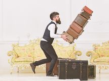 Baggage insurance concept. Porter, butler accidentally stumbled, dropping pile of vintage suitcases. Man with beard and. Mustache in classic suit delivers stock image
