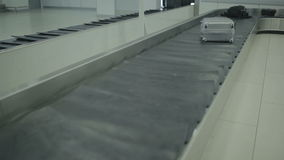 The baggage moves on the luggage conveyor in the airport. Close-up. The camera focuses on the luggage belt of the baggage claim desk at the airport. The luggage stock video footage