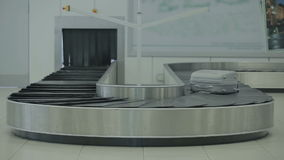 The baggage is moving on the luggage conveyor in the airport. Close-up. The camera focuses on the luggage belt of the baggage claim desk at the airport. The stock video footage