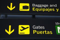 Baggage Reclaim and Departure Gate Sign at Airport. Information sign at international airport written in English and Spanish Stock Photos