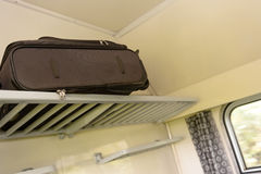 Baggage sitting on train rack in compartment Stock Photos