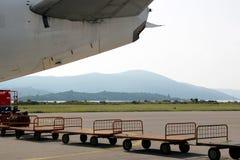 Baggage small carts. Airframe sternpost and baggage small carts Royalty Free Stock Photos