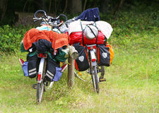 Baggage on touring bikes. Closeup of two touring bicycles loaded with luggage or baggage in countryside Royalty Free Stock Images