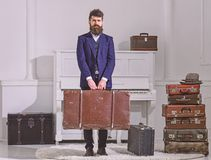 Baggage and travelling concept. Man, traveller with beard and mustache with baggage, luxury white interior background. Macho stylish on strict face stands and royalty free stock photo