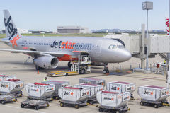 Baggage trucks and Jetstar aircraft at Brisbane Airport Stock Image