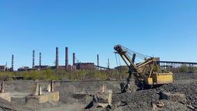 Bagger auf dem Hintergrund des Industriegebiets Stockfotografie