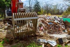 Bagger baut defektes Haus nach Tragödie auseinander lizenzfreies stockfoto