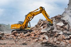 Bagger, der an der Demolierung eines alten industriellen buildin arbeitet Lizenzfreie Stockfotos