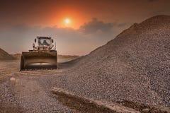 Bagger in einem Steinbruch der Steinumwandlung im Kies für den Bau einer Straße stockbild