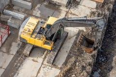 Bagger an an einer Baustelle, am Abzugsgraben, an der Rekonstruktion der Kommunikation entlang Straßen und an den Pflasterungen stockfotos