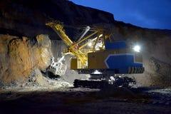 Bagger funktioniert in einem Steinbruch nachts Stockfotografie