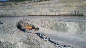 Bagger gräbt Asbestfelsen, um Kipplasterkarosserie zu laden stock footage