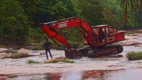 Bagger Grabbing Water vom flachen Fluss gegen Dschungel stock footage