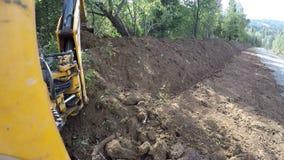 Bagger mit dem Eimer, der einen Graben gräbt stock footage