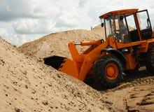 Bagger mit Sand im Eimer Lizenzfreie Stockfotografie