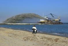 Bagger pumpt Sand auf Strand Stockfoto