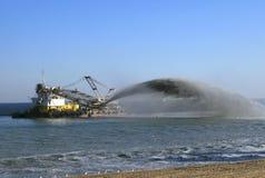 Bagger pumpt Sand auf Strand Stockbilder