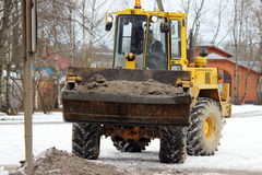 Bagger säubert die Straße in der Stadt des schmutzigen Schnees Lizenzfreie Stockbilder