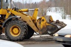 Bagger säubert die Straße in der Stadt des schmutzigen Schnees Stockfotografie