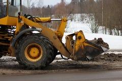 Bagger säubert die Straße in der Stadt des schmutzigen Schnees Stockfoto