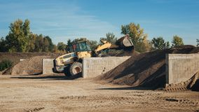 Bagger scooping gravel at construction aggregate dumps. At concrete production plant Stock Images