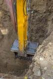 Baggerarm, der suchende gebrochene Abwasserleitung des tiefen Lochs gräbt Lizenzfreie Stockfotos