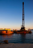 Baggerbetrieb im Seehafen am Sonnenuntergang Stockfotografie