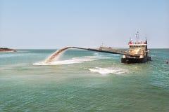 Baggermachineboot die zand en slib verwijderen uit de bodem stock afbeeldingen