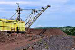 Baggermaschine bei der weltbewegenden Arbeit der Aushöhlung im Steinbruch stockfotos