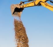 Baggermaschine, die Sand an der Baustelle entlädt Lizenzfreie Stockbilder