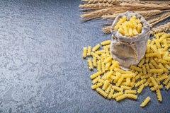 Bagging sack short-cut spiral pasta golden wheat rye ears on bla Stock Photography