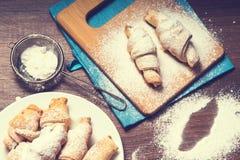 Baglar av smördeg som strilas med pudrat socker arkivbild