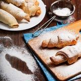 Baglar av smördeg som strilas med pudrat socker Royaltyfria Foton