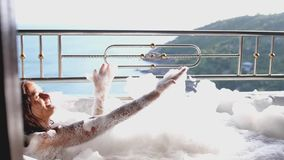 Bagnando la giovane donna dell'attrazione che si rilassa in vasca di innalzamento della schiuma La bella ragazza sorridente gode  stock footage