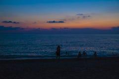 Bagnanti su una spiaggia del mare dopo il tramonto fotografia stock libera da diritti