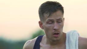 Bagni dell'atleta bello del sudore che ha resto dopo l'allenamento faticoso, sport stock footage